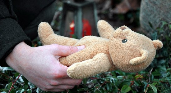 Woman in cemetery in deep sadness about death and loss puts a teddy to grave of her child